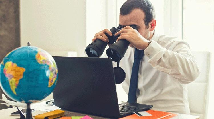 Mann ser på laptop med kikkert